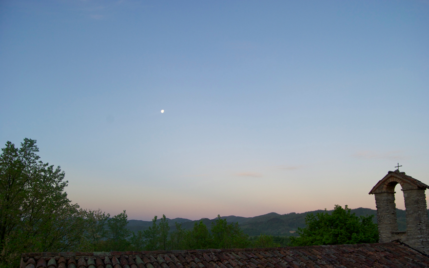 A sunset on Casa della Pace, the moon still high in the sky.